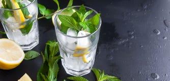 Verres avec de la glace et citron, menthe et glace sur un fond noir Photographie stock