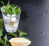 Verres avec de la glace et citron, menthe et glace sur un fond noir Photo stock