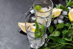 Verres avec de la glace et citron, menthe et glace sur un fond noir Image stock