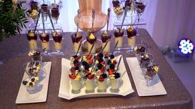 Verres avec des bonbons et des fruits, mûres, fraises, guimauves, cacao banque de vidéos