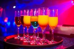 Verres avec des cocktails pour la partie dans la boîte de nuit colorée avec le fond lumineux de couleur Image stock