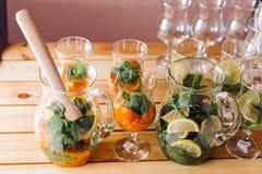 Verres avec des ingrédients pour les cocktails, la menthe et l'orange-3 Photographie stock