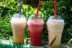 Verres avec des smoothies d'ananas, de mangue et de pastèque Boissons non alcoolisées, nutrition Image libre de droits