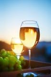 Verres avec du vin blanc au coucher du soleil, avec la réflexion des maisons Images stock