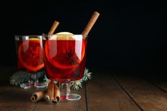 Verres avec du vin chaud rouge sur la table en bois sur le fond foncé image stock