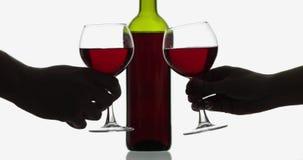 Verres avec du vin ros? Verres de vin avec le vin rouge sur le fond blanc banque de vidéos