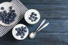 Verres avec du yaourt, les baies et la granola sur la table photo libre de droits