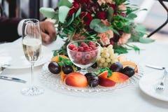 Verres avec la boisson de champagne dans des mains de jeunes mariés Boire heureux de nouveaux mariés Les couples affectueux ont c Photographie stock libre de droits