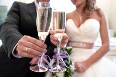 Verres avec le champagne dans les mains des jeunes mariés Photographie stock libre de droits