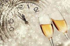 Verres avec le champagne et l'horloge près du minuit Image libre de droits