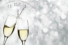 Verres avec le champagne et l'horloge près du minuit Photographie stock