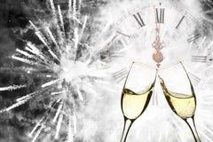 Verres avec le champagne et l'horloge près du minuit Photographie stock libre de droits