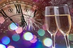 Verres avec le champagne et l'horloge près du minuit Photo stock
