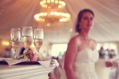 4 verres avec le champagne et la jeune mariée à l'arrière-plan Images libres de droits