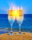 Verres avec le champagne près de la mer Photo stock