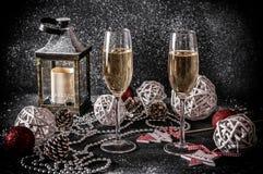 Verres avec le champagne sur un fond noir avec la neige et les décorations Photographie stock
