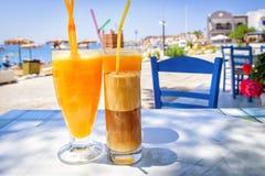 Verres avec le jus d'orange et le milk-shake grec de café Photos libres de droits