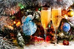 Verres avec le vin mousseux sur le fond de l'arbre de Noël décoré Guirlande avec des lumières, tresse éclatante Images stock