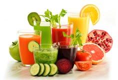 Verres avec les jus organiques frais de légume et de fruit sur le blanc Image stock