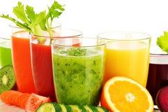 Verres avec les jus organiques frais de légume et de fruit sur le blanc Photo libre de droits