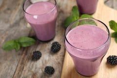 Verres avec les smoothies savoureux de yaourt de mûre photographie stock libre de droits