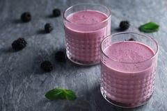 Verres avec les smoothies savoureux de yaourt de mûre photo stock