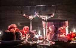 Verres, cadeau et bonbons de vin pendant une soirée romantique Images libres de droits