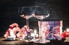 Verres, cadeau et bougies de vin pour la soirée romantique Photo stock