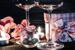 Verres, cadeau et bougies de vin pour la soirée romantique Image stock