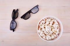 verres 3D avec le maïs éclaté qui se trouvent sur la surface de la table Photos libres de droits