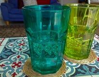 Verres d'eau colorés sur la table basse orientale Photographie stock libre de droits