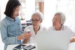 Verres d'eau donnants ou servants de petite-fille mignonne pour la grand-mère pour boire, la femme asiatique heureuse, les soeurs photos libres de droits