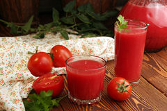 Verres d'OE, cruche de jus de tomates et tomates fraîches Photographie stock