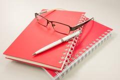 Verres d'oeil avec le carnet et le stylo Photographie stock libre de droits