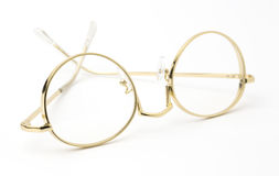 Verres d'oeil d'or pliés d'isolement sur le blanc Image stock