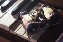 Verres d'opéra sur le piano photo stock