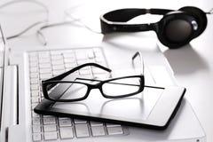 Verres d'ordinateur portable et comprimé numérique sur le blanc Photos stock