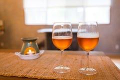 Verres de bière avec du temps romantique de lampe d'arome à la cheminée Images stock