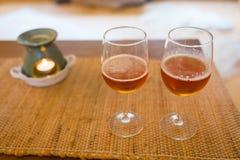 Verres de bière avec du temps romantique de lampe d'arome à la cheminée Images libres de droits