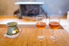 Verres de bière avec du temps romantique de lampe d'arome à la cheminée Photos libres de droits