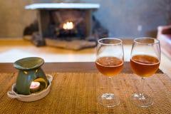 Verres de bière avec du temps romantique de lampe d'arome à la cheminée Image stock