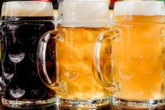 Verres de bière blonde et foncée sur un compteur de barre publication image stock