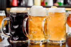 Verres de bière blonde et foncée sur un compteur de barre publication photos stock