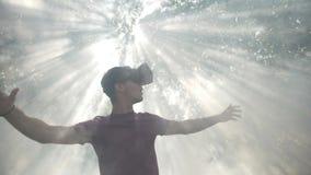 Verres de casque de la réalité virtuelle VR sur la nature et le soleil les explorant de cyberespace de l'homme dans le mouvement  banque de vidéos