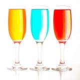 Verres de champagne avec les liquides colorés se tenant dans une rangée Image libre de droits