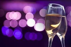 Verres de Champagne contre des lumières de vacances images stock