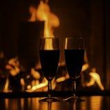 Verres de champagne rouge par la cheminée Photographie stock