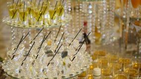 Verres de champagne de scintillement et de casse-croûte délicieux sur une table de buffet banque de vidéos