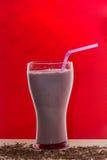 Verres de cocktail de lait avec la fraise, la crème glacée du plat en bois et le fond rouge Boissons de bonbon pour le concept d' Images stock