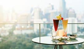 Verres de cocktail sur la table dans la barre de dessus de toit contre la vue de ville, anniversaire romantique de datation Image stock